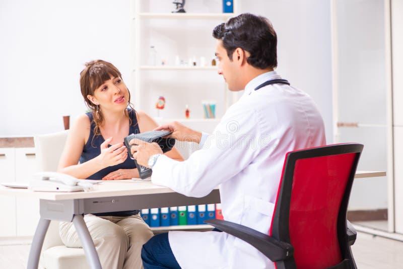 检查妇女的血压的年轻医生 免版税图库摄影