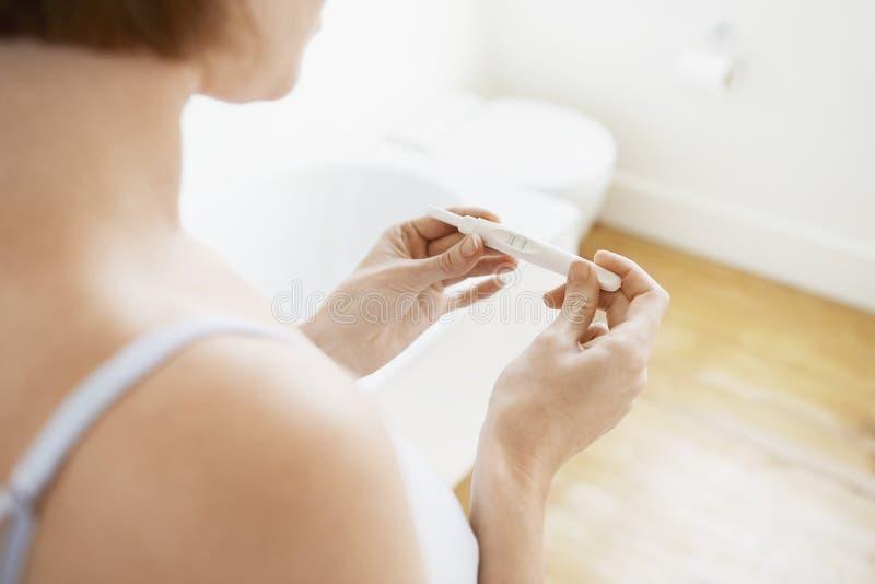 检查妊娠试验成套工具的妇女 库存图片