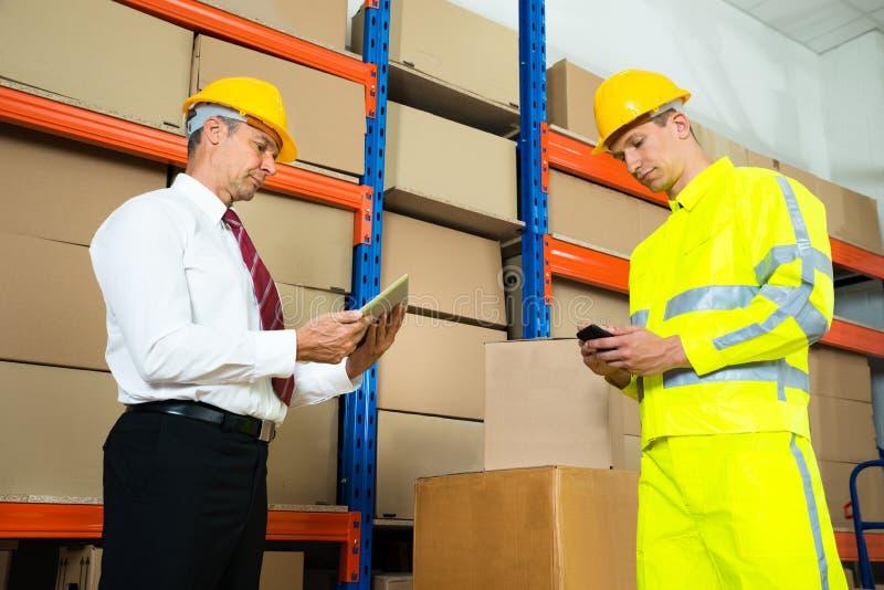 检查存货的仓库工作者与经理 免版税库存照片