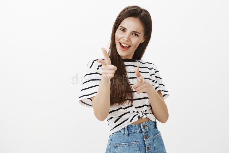 检查它,巨大提议您 快乐的激动的女性女孩画象牛仔布裙子和镶边T恤杉的,指向 免版税图库摄影