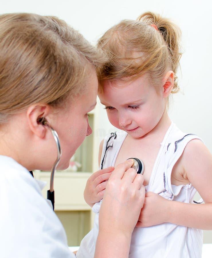 检查小女孩的医生 免版税图库摄影