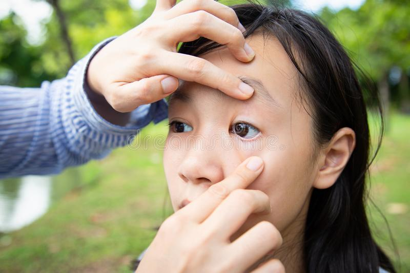检查小孩女孩耐心疼痛眼睛,女儿感觉眼睛痛苦,妇女审查的眼睛的手母亲特写镜头亚洲人 免版税库存照片