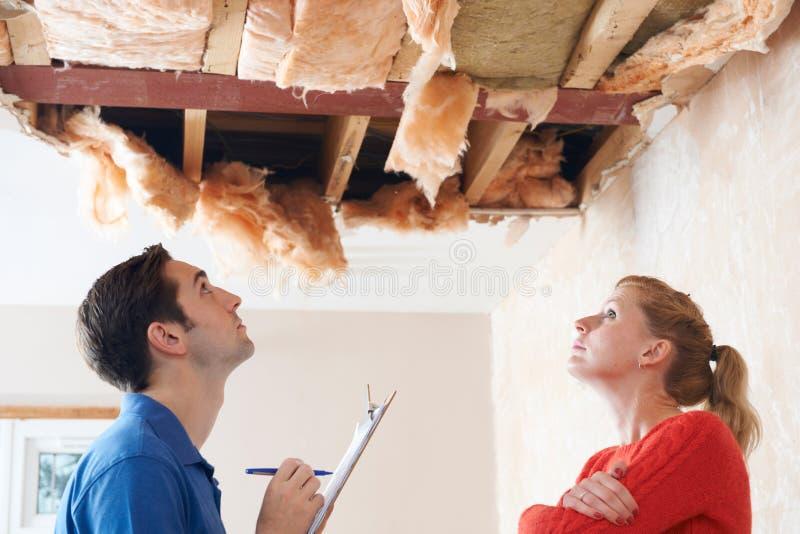 检查屋顶损伤的建造者和客户 库存照片