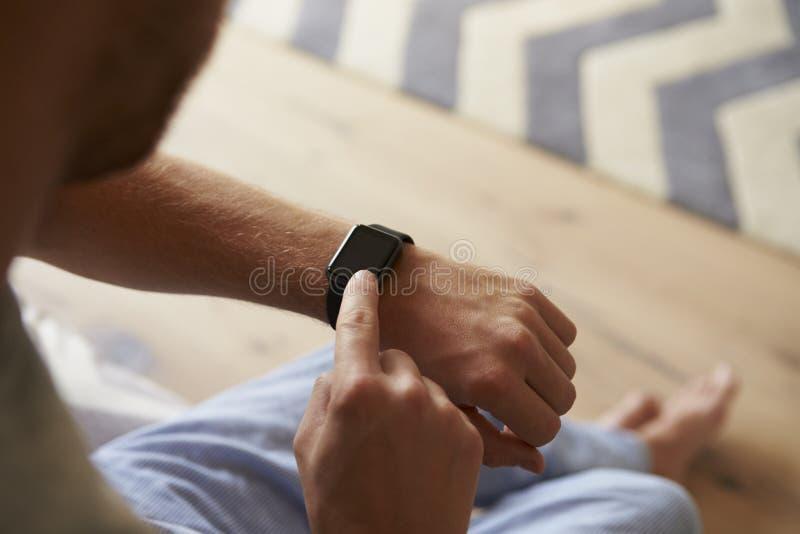 检查巧妙的手表的人佩带的睡衣在卧室 库存照片