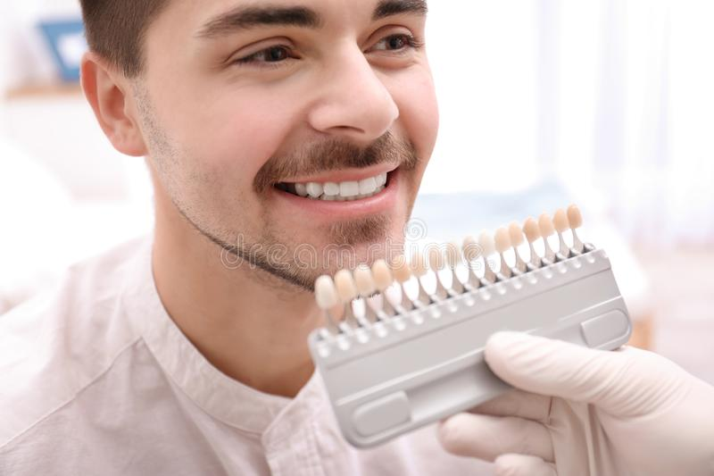 检查年轻人的牙颜色的牙医 免版税库存照片