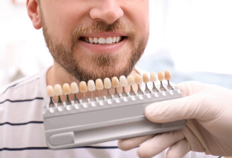 检查年轻人的牙颜色的牙医 免版税库存图片
