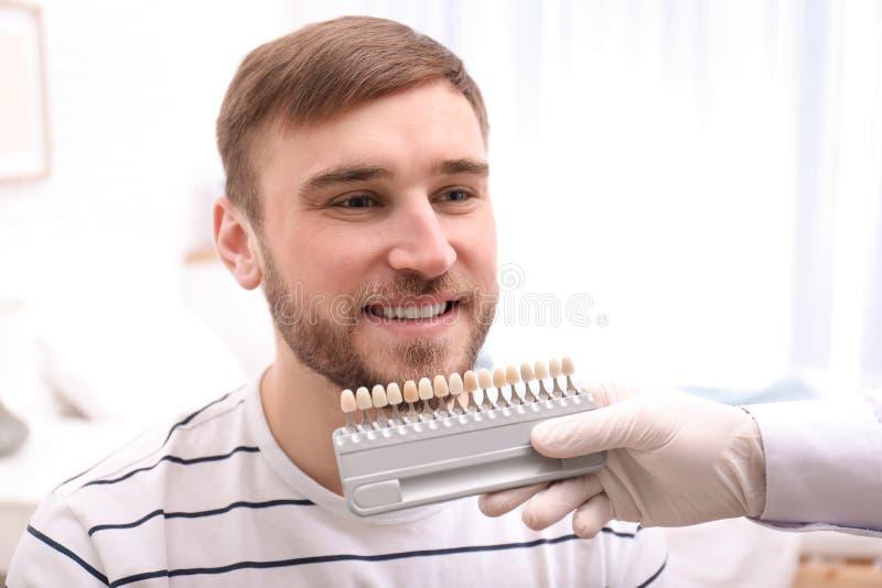检查年轻人的牙颜色的牙医 库存照片