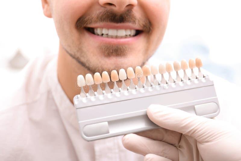 检查年轻人的牙颜色的牙医 图库摄影