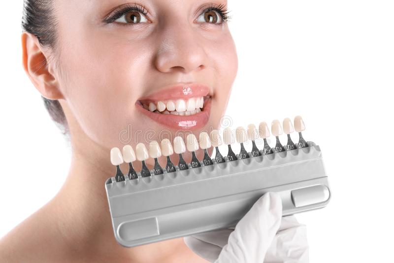 检查年轻女人的牙颜色的牙医 免版税库存图片