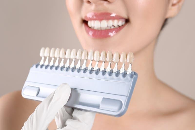 检查年轻女人的牙颜色的牙医 免版税库存照片