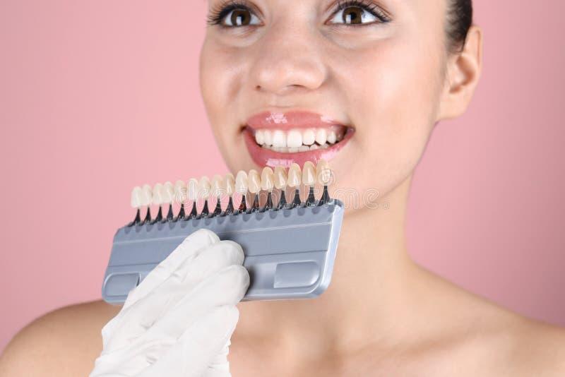 检查年轻女人的牙颜色的牙医 库存照片