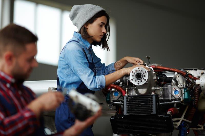 检查引擎的女性技工在车间 免版税库存照片