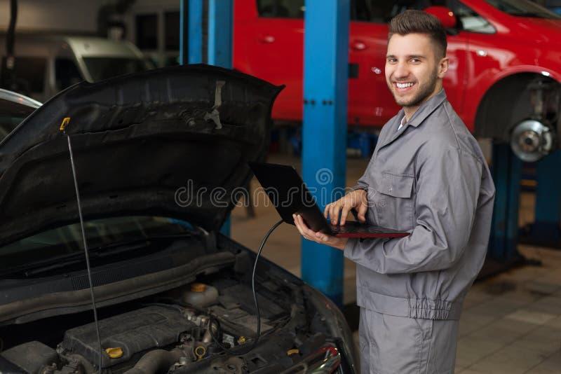 检查引擎的汽车机械师 免版税库存图片