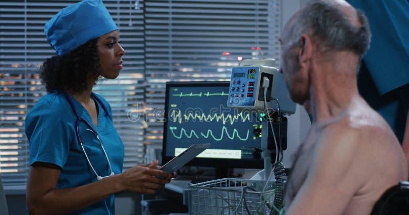 检查患者心率的女性医生 图库摄影