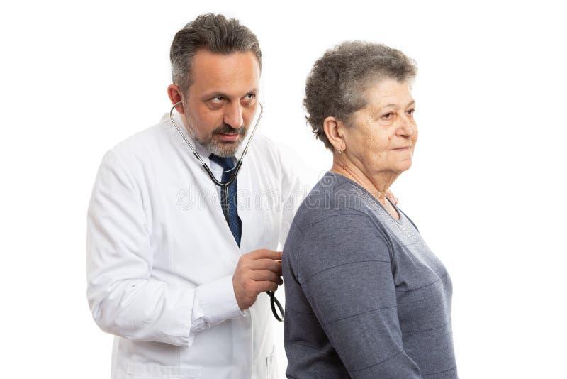 检查患者的军医通过听与听诊器 免版税库存图片