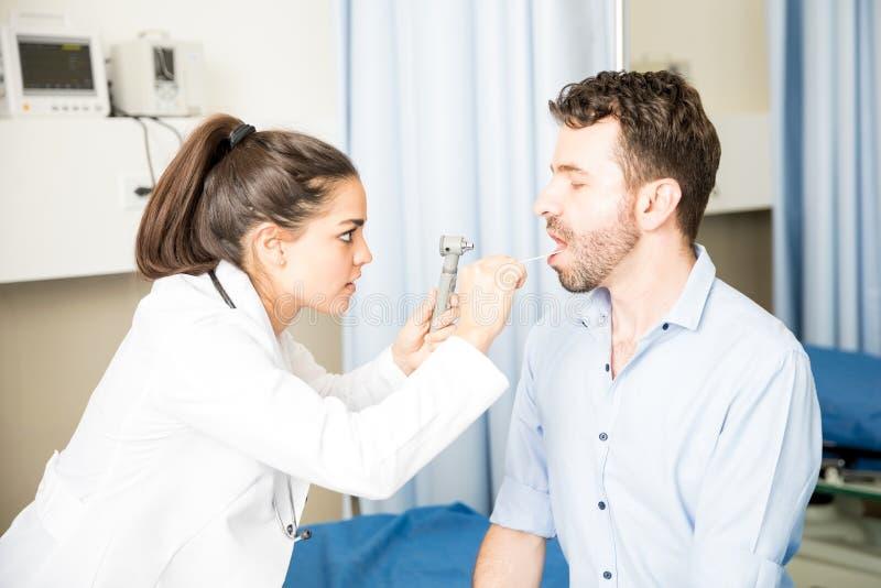 检查患者的喉头的眼科医生 库存图片