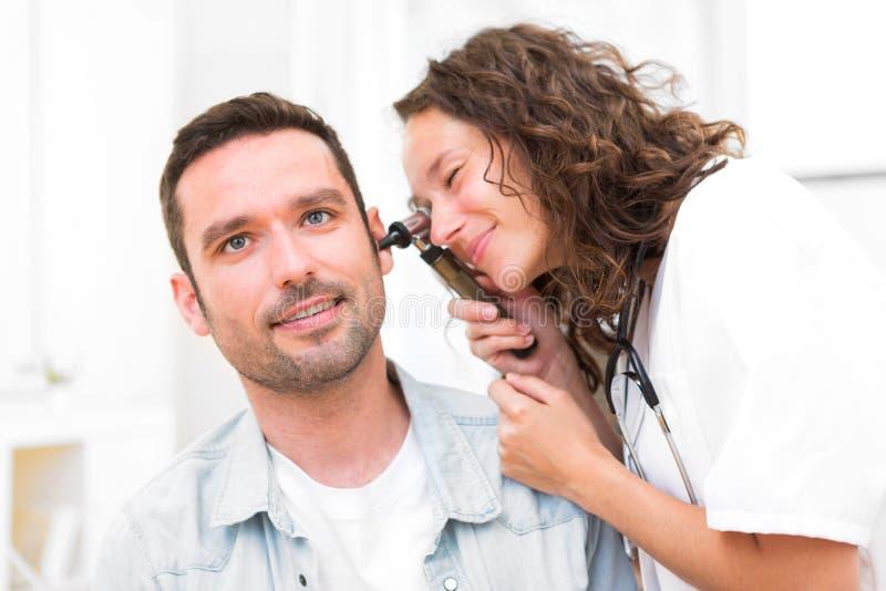 检查患者的耳朵的年轻可爱的医生 库存图片