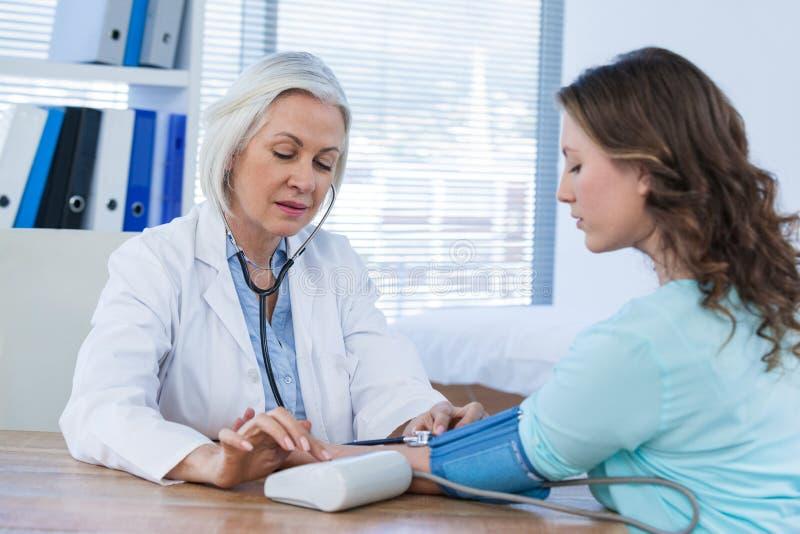 检查患者的血压的女性医生 库存照片