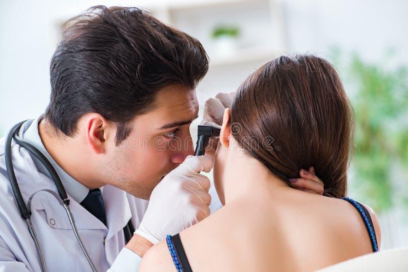 检查患者耳朵的医生在身体检查期间 免版税图库摄影