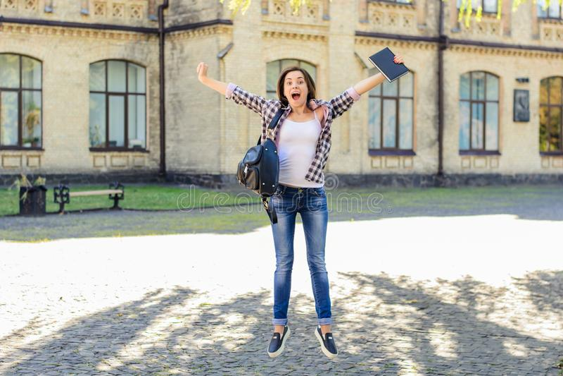检查成就好luch教育学院大厦概念 庆祝愉快的激动的跳跃的女学生胜利和 前 免版税库存照片