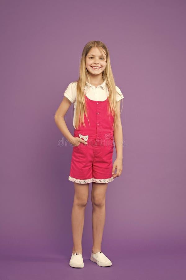 检查我的成套装备 青少年时尚概念 摆在时髦的总体,紫罗兰色背景的女孩愉快的笑容 孩子女孩 库存照片