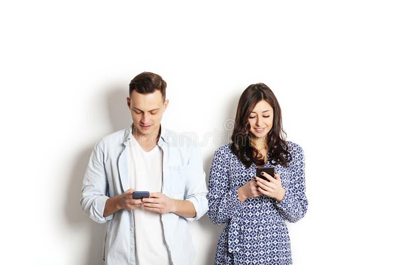 检查手机的年轻夫妇,读消息 技术&关系概念 现代言情麻烦 男性&女性o 库存照片
