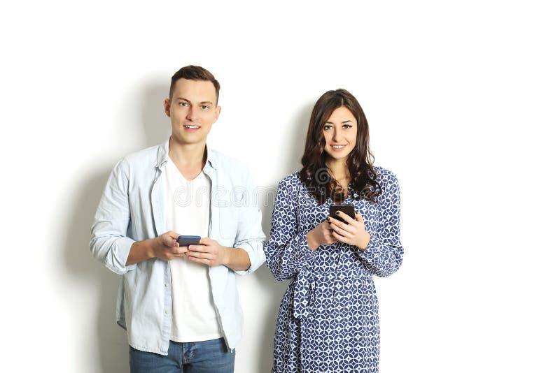 检查手机的年轻夫妇,读消息 技术&关系概念 现代言情麻烦 男性&女性o 免版税库存照片
