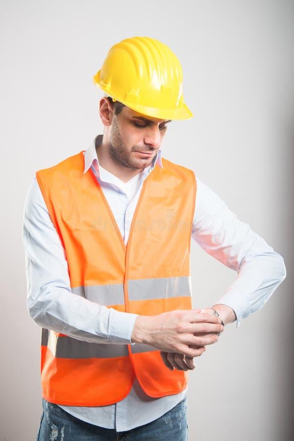 检查手表的年轻建筑师画象 免版税库存图片