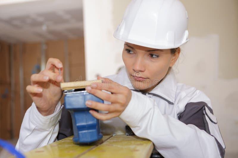 检查打破的工具的妇女建造者 图库摄影