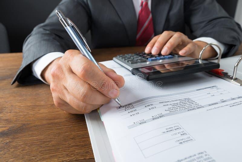 检查收据的商人在书桌 免版税库存图片