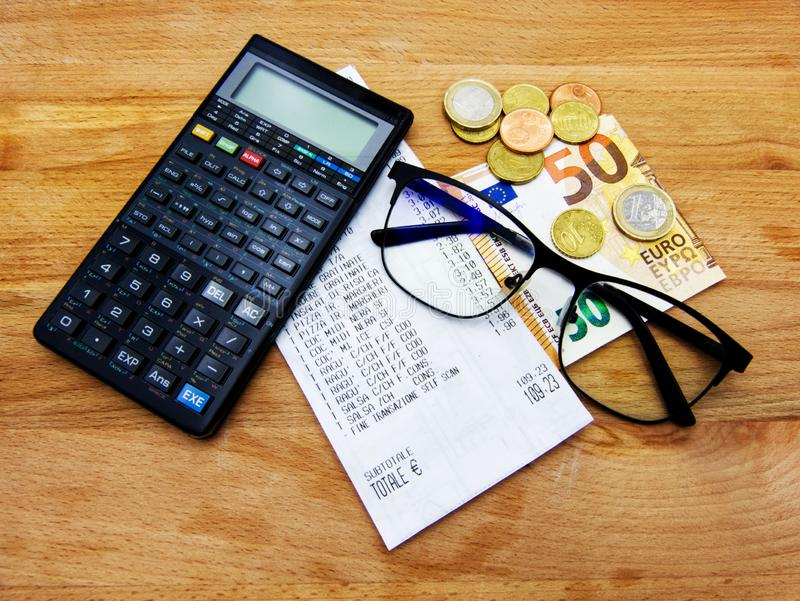 检查收据 计算器、玻璃和金钱 购买力量的概念 免版税库存图片