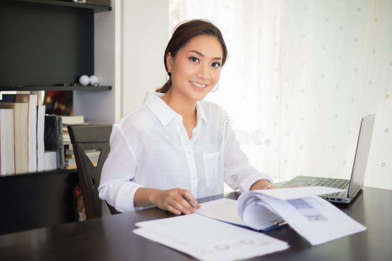 检查文件和使用noteb的美丽的亚裔女商人 库存图片