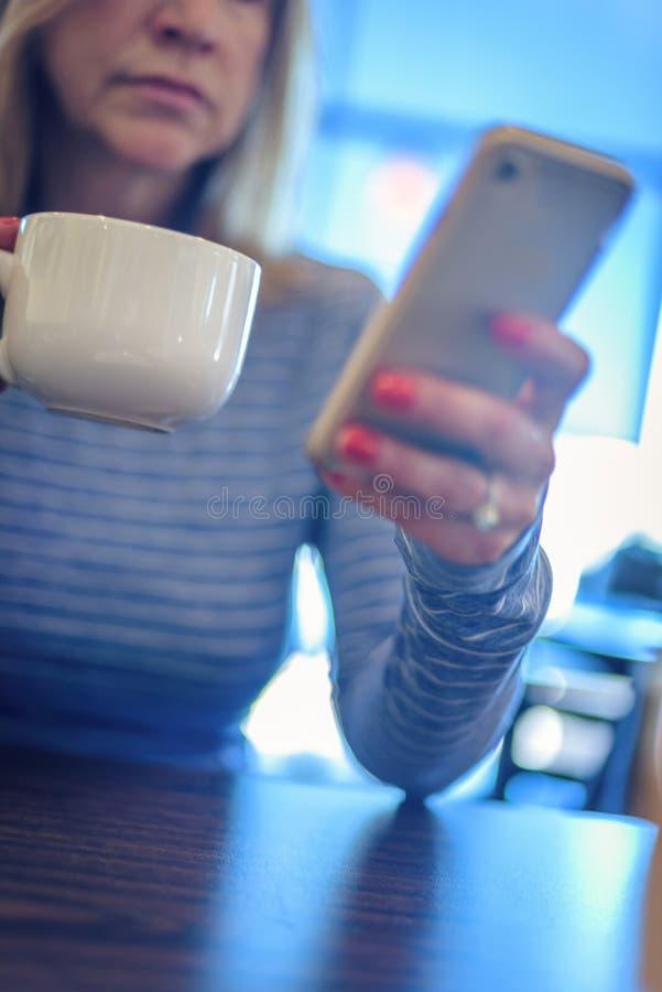 检查智能手机和举行杯子c的妇女有角度的特写镜头 库存图片