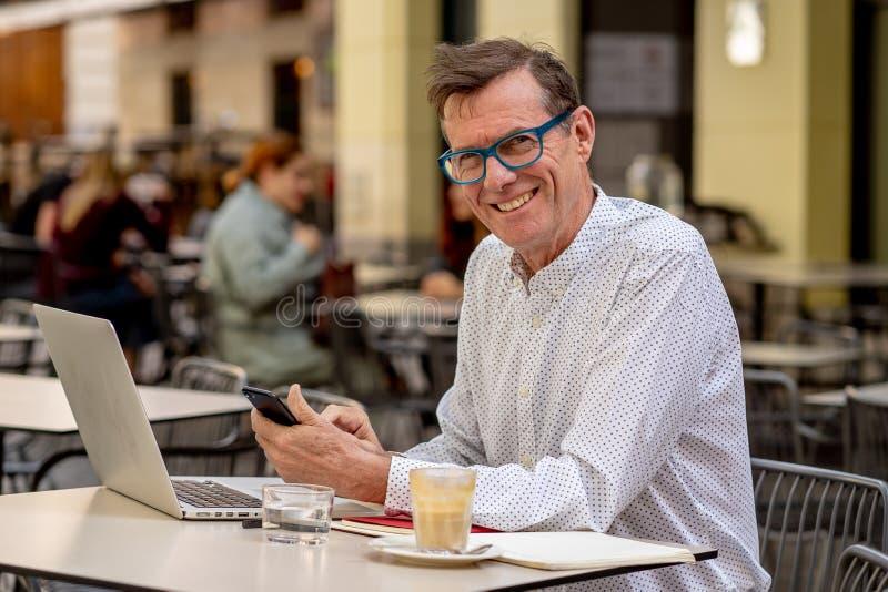 检查智能手机的微笑的老人,当研究计算机在大阳台使用现代技术时的前辈的户外咖啡馆 库存照片