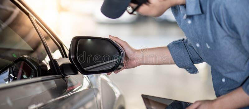 检查汽车后视镜的亚裔汽车机械师 免版税图库摄影