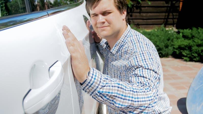 检查汽车油漆的年轻微笑的人特写镜头画象在买新的汽车前 库存图片