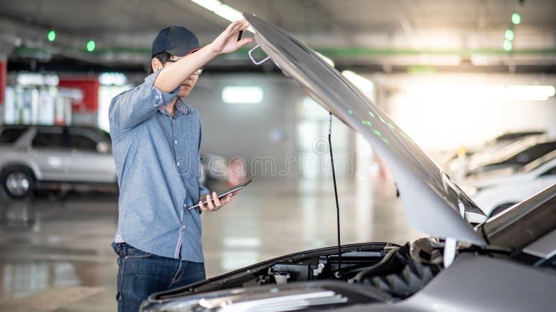检查汽车的亚裔汽车机械师使用片剂 库存图片