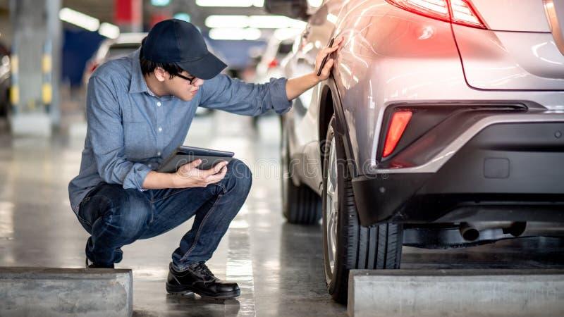 检查汽车的亚裔汽车机械师使用片剂 免版税库存照片