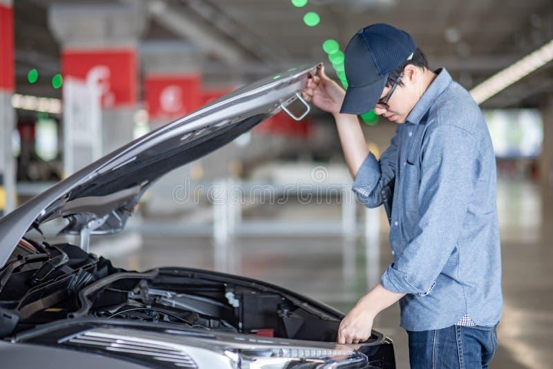 检查汽车的亚裔汽车机械师 免版税库存图片