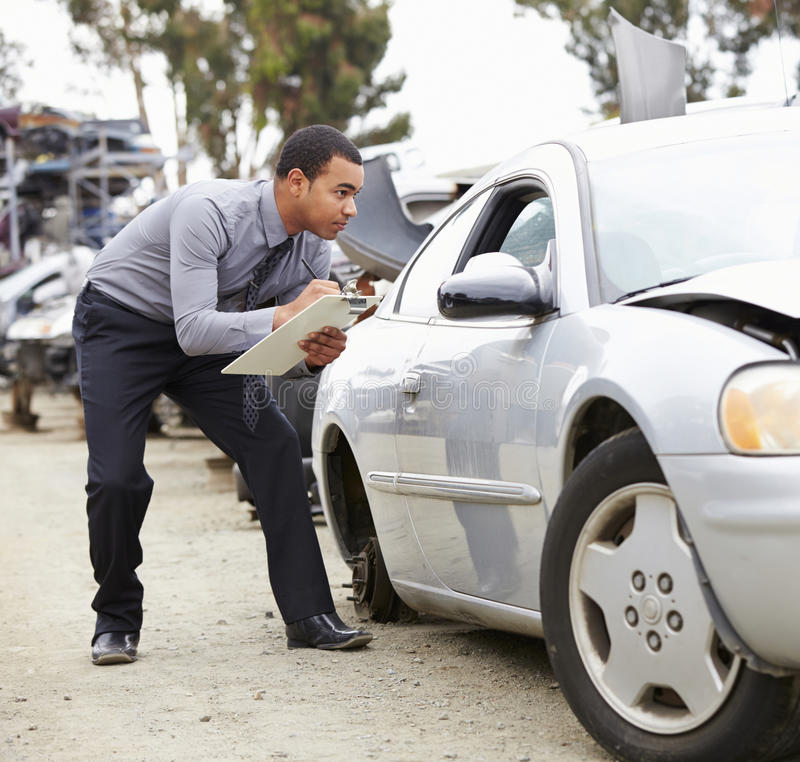 检查汽车的保险赔偿估定员介入在事故 免版税库存照片