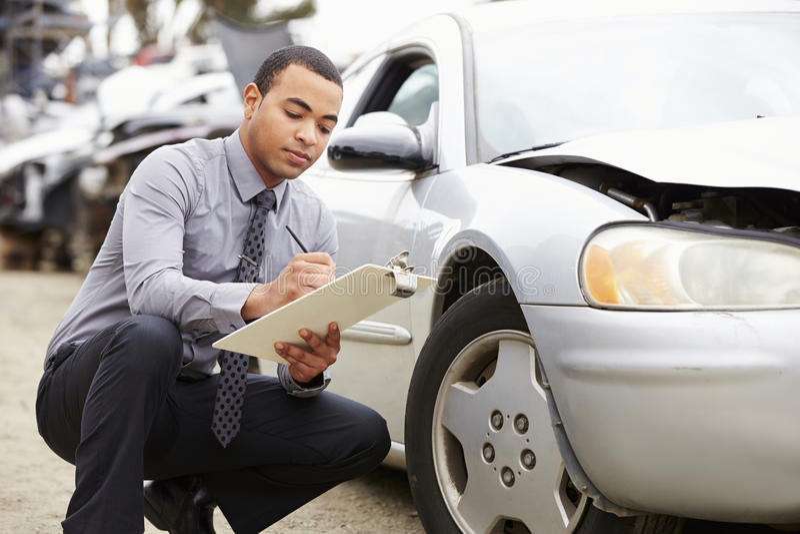 检查汽车的保险赔偿估定员介入在事故 免版税图库摄影