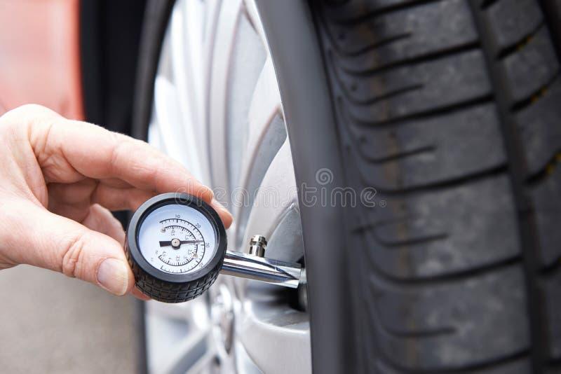 检查汽车轮胎气压的人特写镜头与测量仪 免版税库存图片