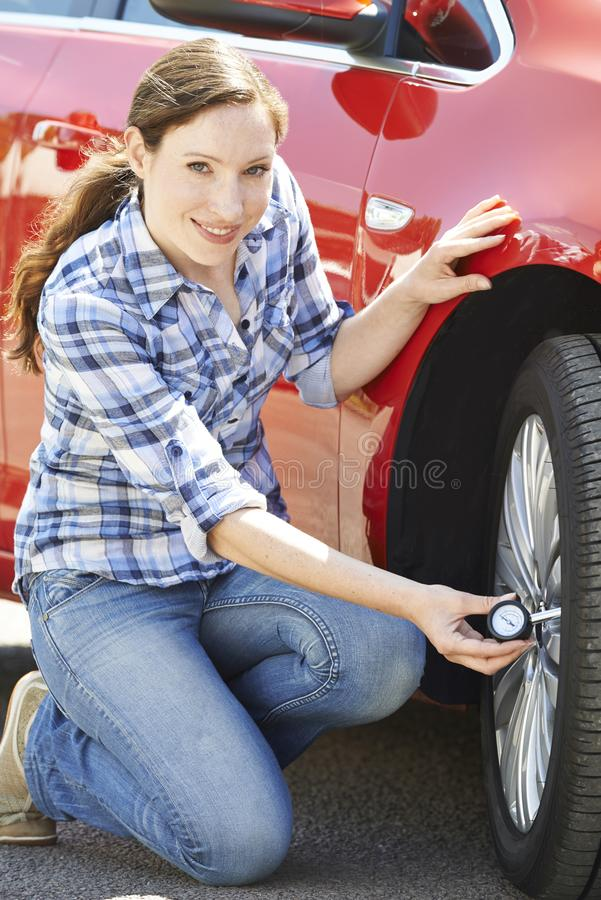 检查汽车轮胎气压的妇女画象使用测量仪 免版税库存照片