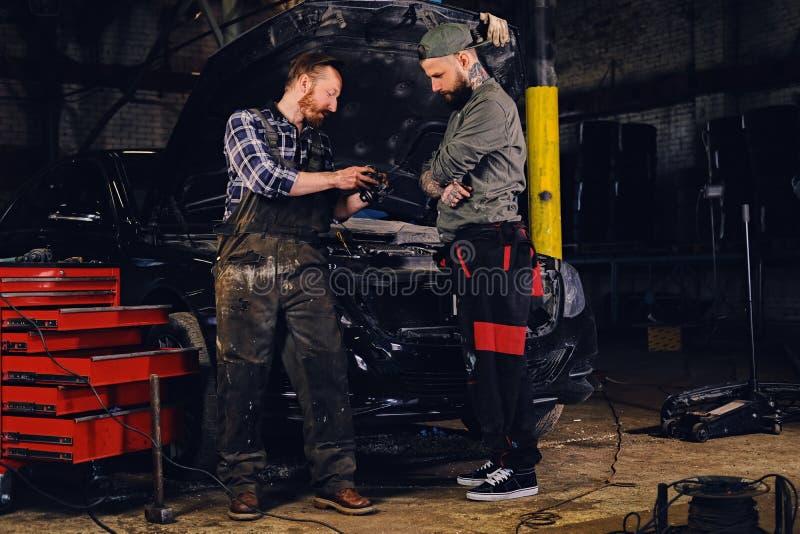 检查汽车` s发动机零件的两位有胡子的技工 库存照片
