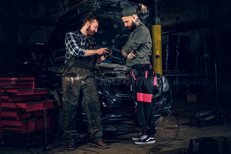 检查汽车` s发动机零件的两位有胡子的技工 库存图片