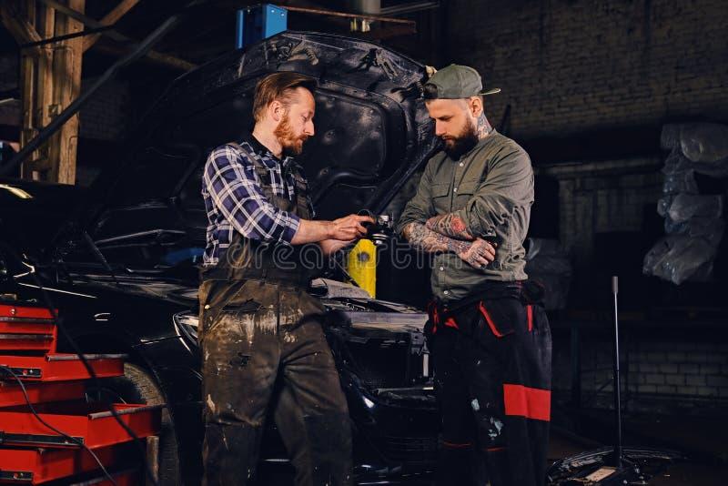 检查汽车` s发动机零件的两位有胡子的技工 免版税图库摄影