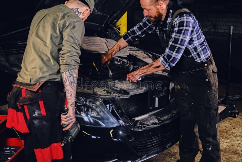 检查汽车` s发动机零件的两位有胡子的技工 免版税库存图片