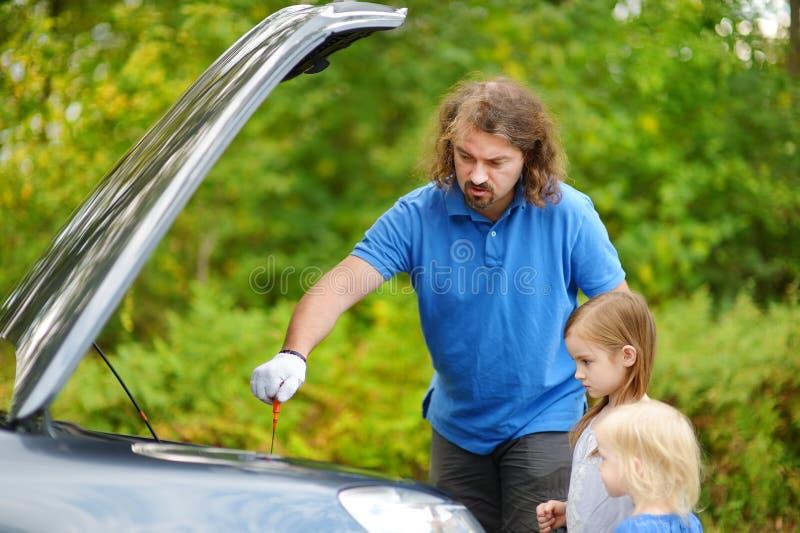 年轻检查油面的父亲和他的女儿 库存图片