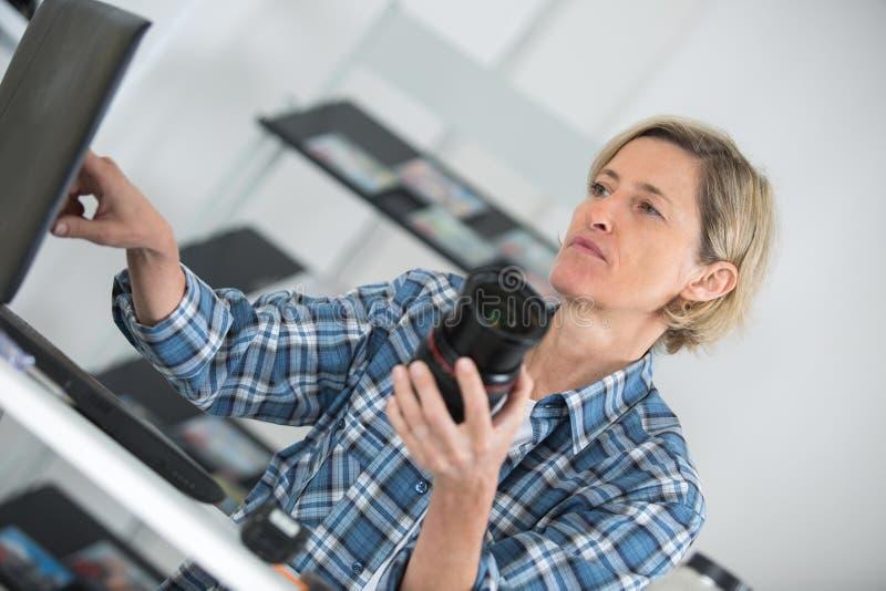 检查照片秘密审议的女性食物摄影师 免版税库存图片