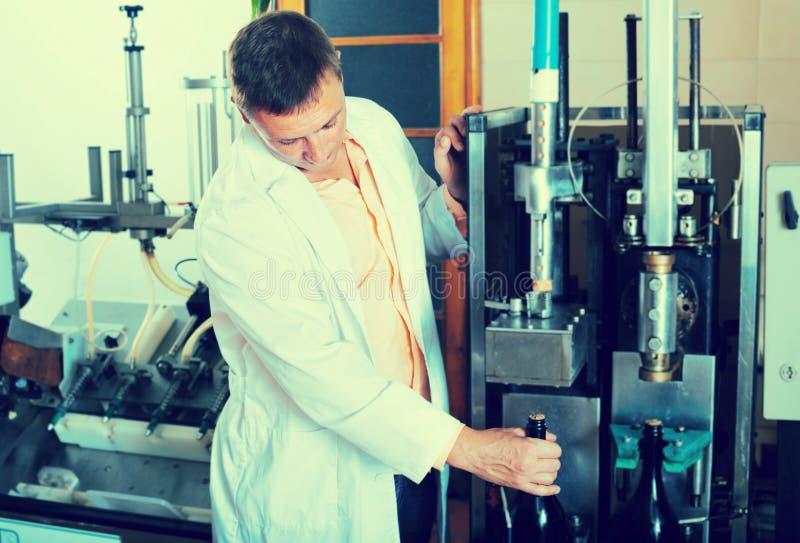 检查瓶的质量的专业传动机工作者 免版税库存照片